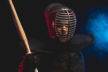 Portrait Of Young Kendo Fighter With Shinai Bamboo Sword Isolated Over Smoky Space. Tradition Kendo Armor, Samurai
