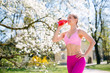 Fit woman having break from outdoor exercise in spring