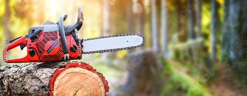Chainsaw on wooden stump or firewood. Fototapete