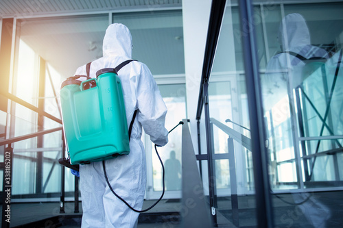 Fototapeta Unrecognizable person in white protection suit disinfecting public areas to stop spreading highly contagious coronavirus. Man with tank reservoir on his back spraying disinfectant to kill COVID-19. obraz