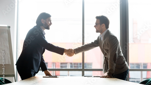 Photo Smiling male business partners shake hands greeting getting acquainted at meetin