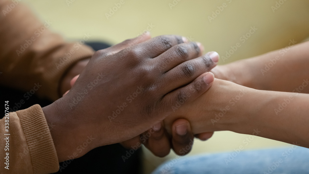 Fototapeta Close up african american man hands holding upset depressed woman, comforting wife for supporting frustrated disappointed girlfriend having life problem, showing love and support.
