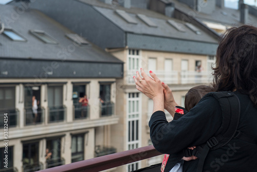 Photo a mother and her baby applauding from the balcony in solidarity with the health