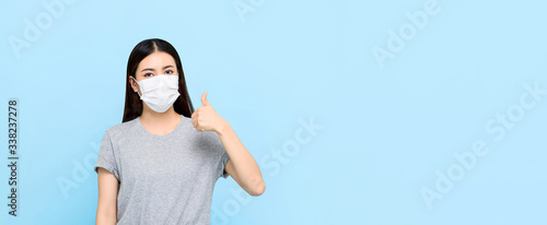 Young Asian woman wearing medical face mask and giving thumbs up isolated on lig Canvas Print