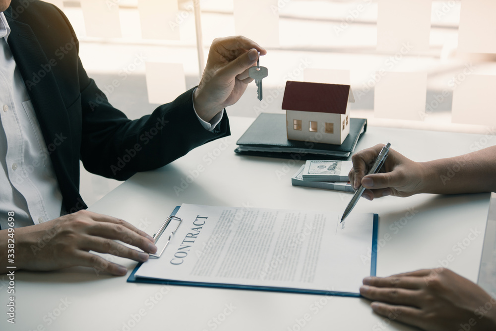 Fototapeta Hand of real estate agent passes the key to new homeowners in office with buyer house concept.