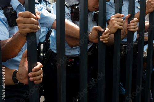Cuadros en Lienzo Midsection Of Police Holding Gate While Standing Outdoor