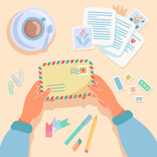 Female Hands Holding Paper Envelope. Post Stamps, Postcards, Pens, Cup Of Coffee Layout On The Table. Top View. Post Crossing, Sending Paper Letters Concept. Flat Cartoon Vector Illustration