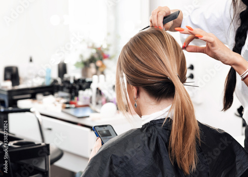 hairdresser does a tail hairstyle for a woman with long brown hair