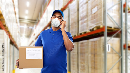 Obraz health, safety and pandemic concept - happy indian delivery man with smartphone and parcel box wearing face protective mask for protection from virus over warehouse background - fototapety do salonu