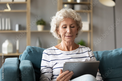 Fotografía Calm mature woman using computer tablet, looking at screen, sitting on couch at