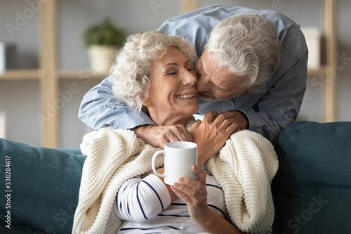 Stampa su Tela Loving older husband kissing smiling wife on cheek, covering warm plaid, express