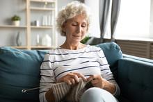 Satisfied Older Woman Knitting, Sitting On Cozy Sofa At Home, Enjoying Leisure Time On Weekend, Mature Senior Female Holding Knitting Needles, Creating Clothes, Elderly Generation Hobby Activity