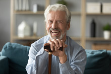 Head Shot Portrait Smiling Mature Man With Walking Stick Sitting On Couch At Home, Happy Older Senior Male Holding Hands On Wooden Cane, Looking At Camera, Elderly People Healthcare Concept