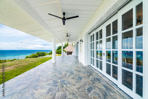 A white patio near dining room, with ceiling fans and full size windows with view of the lawn and sea Wallpaper Mural
