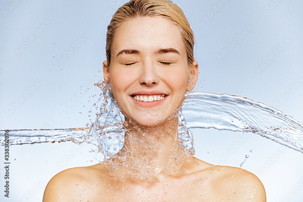 Fototapeta Photo of  young  woman with clean skin and splash of water. Portrait of smiling woman with drops of water around her face. Spa treatment. Girl washing her body with water. Water and body.