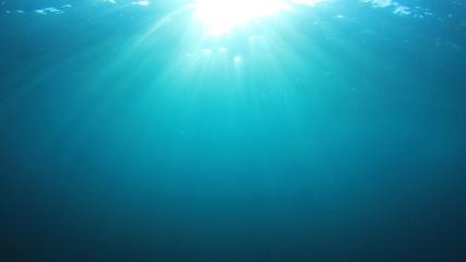 Underwater sunburst. Blue water background and sunlight