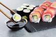Sushi maki with avocado, sushi philadelphia, soy sauce and wasabi. Chopsticks taking portion of sushi roll.