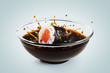 Sushi maki drops in a bowl with soy sauce on light background. Splash of soy sauce.