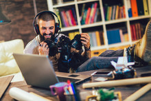 Handsome Tattooed Man Working At Home On Laptop While Sitting At The  Table With Cute Dog