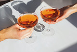 Close up view of man and woman hands holding glasses with cocktail of orange color