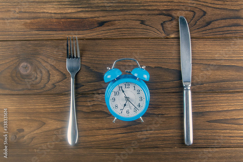 Fototapeta One vintage clock with fork and knife on dark wood table top view