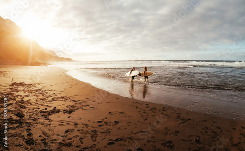 Photo Happy friends surfing together on tropical ocean - Sporty people having fun duri