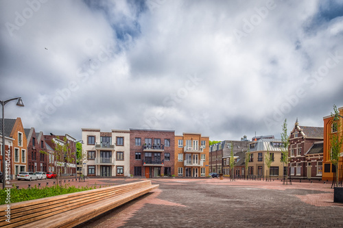 Fotografia, Obraz Empty Road By Buildings Against Sky In City