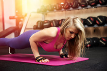 Athletic Woman Making Push-up Exercise In Gym
