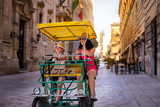Fototapeta Uliczki - Tourist family having fun with tandem bike at the narrow streets of Lecce, Italy