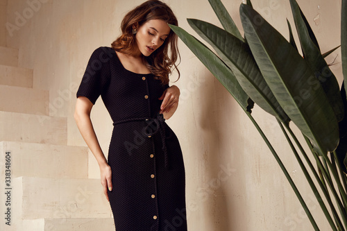 Beautiful woman brunette tanned skin natural makeup wear fashion clothes summer collection black knitted cotton dress on buttons style for summer romantic date interior stairs leaves flowerpot.