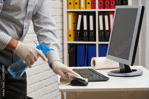 Obraz concept of cleaning or disinfecting the office - a businessman cleans the workplace, computer, desk, uses a spray gun and paper napkins. Cleaning surfaces from microbes, viruses and dirt. - fototapety do salonu