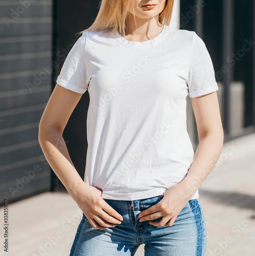 Obraz Girl wearing white t-shirt posing against street , urban clothing style. Street photography - fototapety do salonu