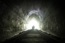 Silhouette People Walking On Railroad Track In Tunnel