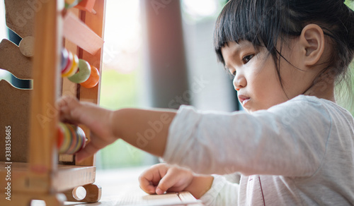 Kids learnfrom play with colourful wooden toy on table top at home Slika na platnu