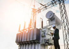 A Low Angle Image Of A Businessman Wearing A Black Suit, Standing Looking At A Large Power Transformer With Blue Sky To Be Background, Concept About Business People Who Want To Invest In Energy