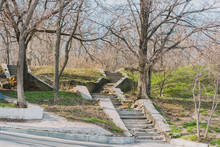 Old Uncared Stairs Made From Stones In Empty Hilly Park With Many Of Trees And  And Green Grass. Nature. Outdoor. Calm. Quiet Place For Relax. Nobody. Environment. Clean. Abandoned. Staircase Up