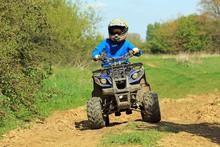 A Teenage Boy Riding A Quad Bi...