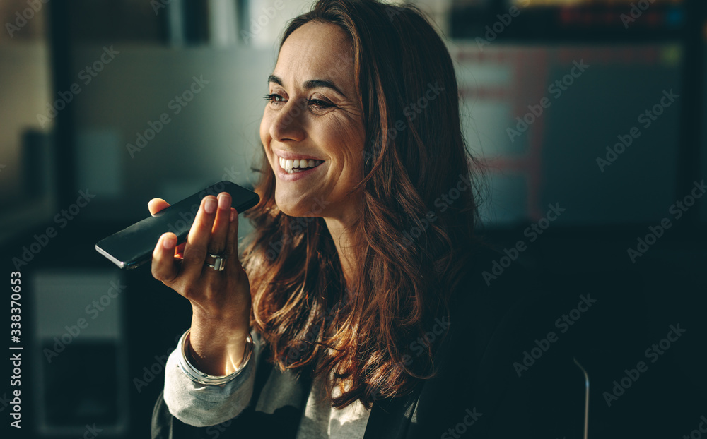 Fototapeta Businesswoman speaking on mobile phone in office