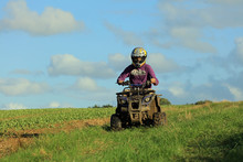 Young Teenage Boy Riding A Quad Bike In The English Countryside.