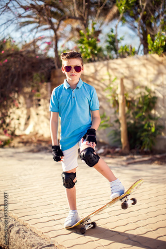 Kid boy with skateboard. Childhood, leasure and lifestyle concept Fototapet