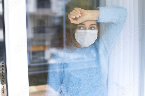 Obraz Young woman in quarantine wearing a mask and looking through the window - fototapety do salonu