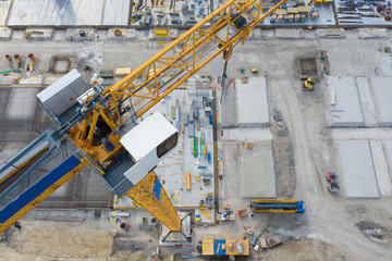 big yellow crane on construction building site with aerial view from top