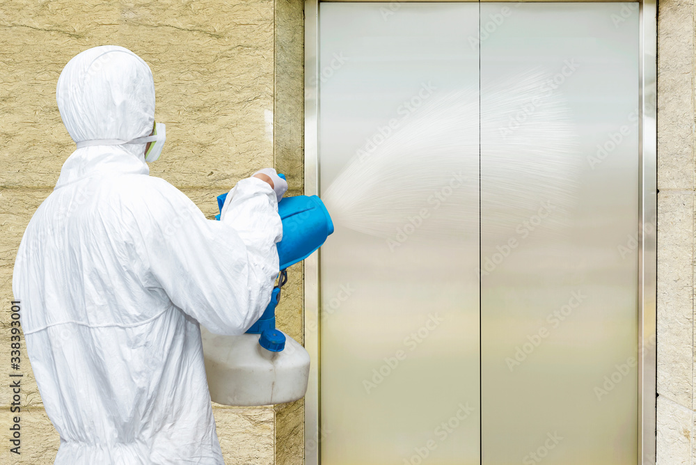 Fototapeta Man in a white protective suit spraying disinfectant in the office building