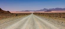 Dirt Road Amidst Desert Against Sky