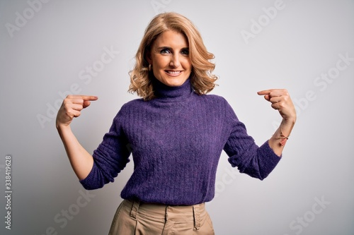 Middle age beautiful blonde woman wearing purple turtleneck sweater over white background looking confident with smile on face, pointing oneself with fingers proud and happy Tableau sur Toile