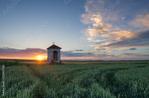 chapel at sunset in the midst of spring fields Fototapet