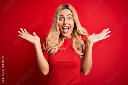 Obraz Young beautiful blonde woman wearing casual t-shirt standing over isolated red background celebrating crazy and amazed for success with arms raised and open eyes screaming excited. Winner concept - fototapety do salonu