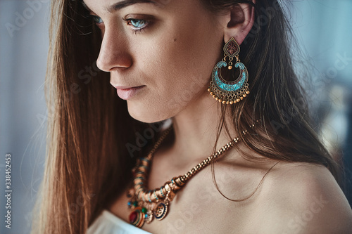 Portrait of stylish sensual brunette boho woman with beautiful eyes wearing big earrings and gold necklace Canvas Print