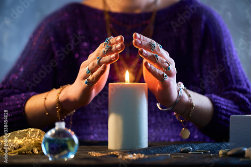 Obraz Fortune teller woman using burning candle flame for spell, witchcraft, divination and fortune telling. Spiritual esoteric occult magic ritual illustration - fototapety do salonu