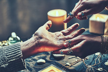 Fortune Teller Woman Wearing Silver Rings With Turquoise Stone And Bracelets Reads Palm Lines During Fortune Telling Around Candles And Other Magic Accessories. Palmistry And Divination